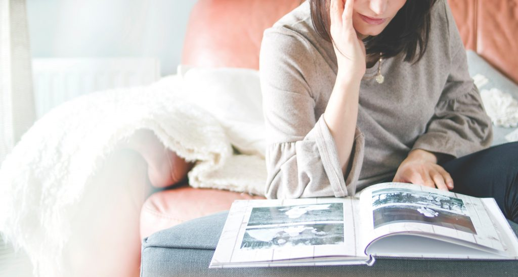 a girl on her bed looking in a photo album