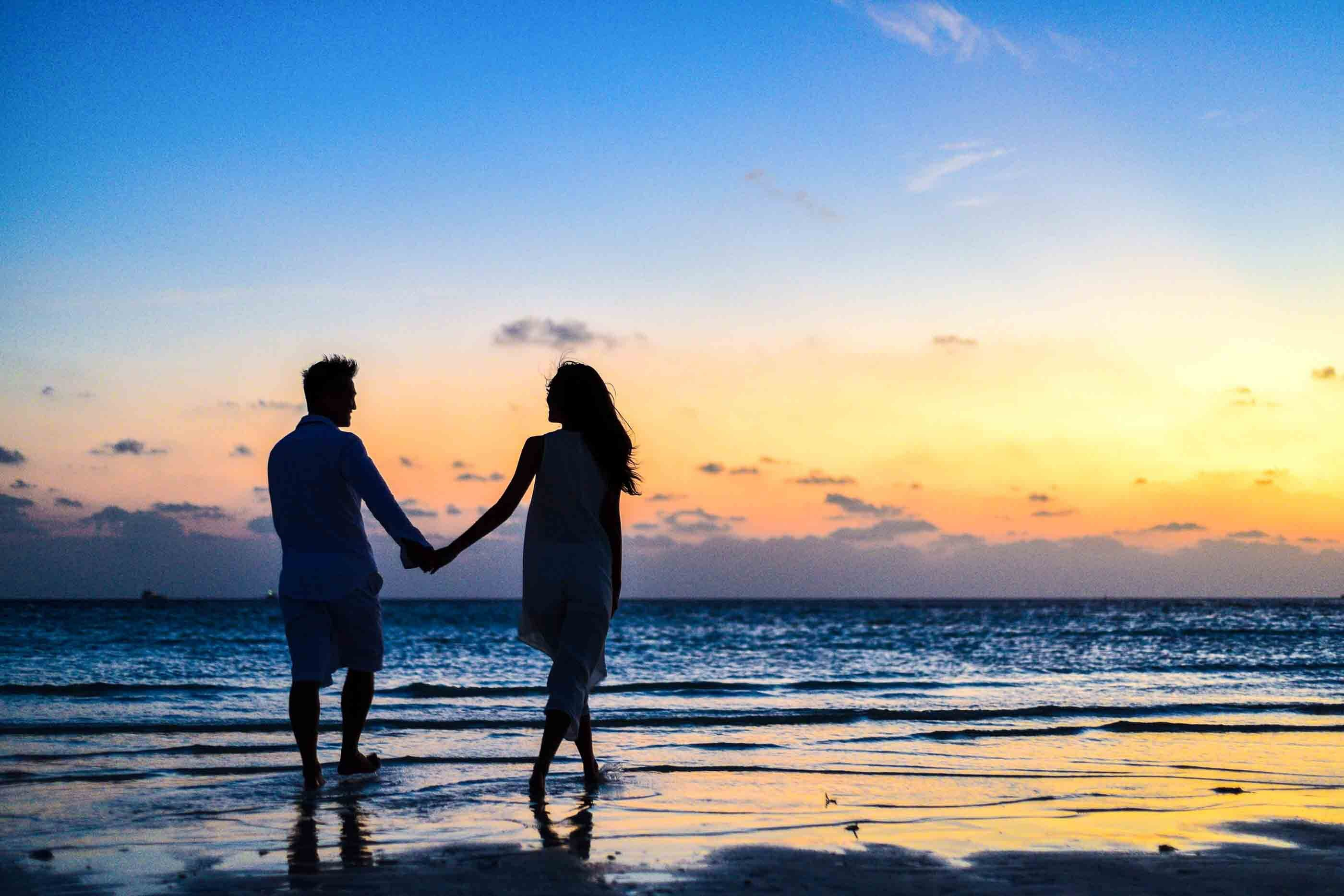 a couple on the beach holding hands