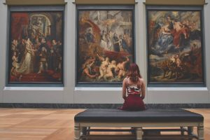 girl sitting in front of some art pictures in a museum